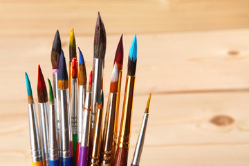 Paint brushes on wooden background. Selective focus