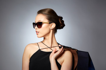 happy woman in black sunglasses with shopping bags