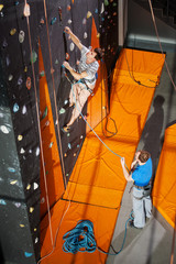 Strong climber is climbing on an indoor rock-climbing wall, his partner standing on the ground belaying the climber