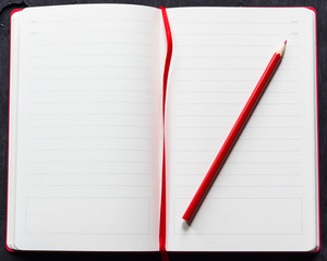 Red notebook with pencil on a black wooden background