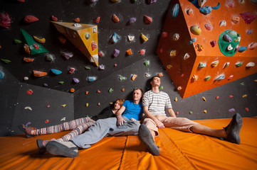 Three tired climbers with closed eyes sitting on the orange mat near rock wall indoors. Bouldering