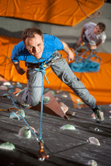 Man with climbing equipment hanging on a rope an indoor rock-climbing wall, view from above