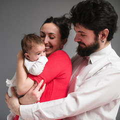 father hugs his wife and daughter