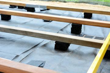 Unterkonstruktion für Terrasse mit Holzbalken und Terrassenpads aus Granulat und Bautenschutzmatte