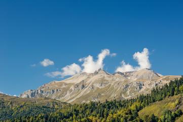 Вид на высокий хребет Кавказских гор и лес у подножья