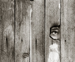 the eyes of a man spying through a hole in an old wooden fence. with space for posting information. black and white photo