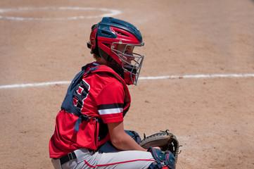 Teen baseball catcher behind home plate.