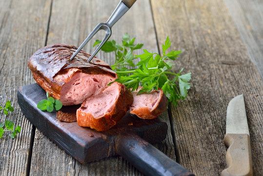 Ofenfrischer bayerischer Leberkäse rustikal auf einem Holzbrett serviert - Bavarian meat loaf on a wooden cutting board
