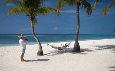 couple taking picture at the perfect beach on hammock, Maldives