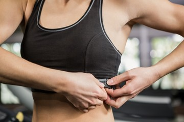 Woman in gym wearing heart rate monitor around her chest