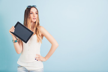 Girl in summer dress posing on a blue background. She hold a tablet in one hand and looks in the side. Empty space for text.
