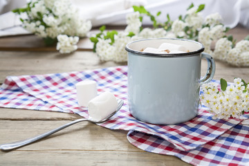 Hot cocoa chokolate with marshmallows in blue cup on checkered napkin and spring blossoms.