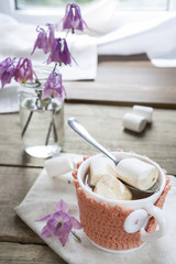 Hot cocoa with marshmallows in cup and cup crochet holder and fresh spring pink bell flowers on wooden table