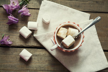 Hot cocoa with marshmallows in cup and cup crochet holder and fresh spring pink bell flowers on wooden table. Coloring and processing photos in vintage style with vintage selective focus.