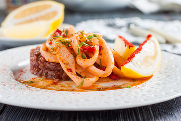 fried squid rings with red rice, paprika and lemon