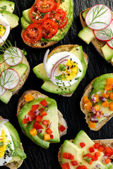 Avocado canapes  with various toppings on a black stone background