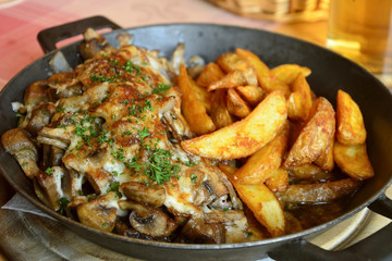 Pork steak with fried mushrooms and onions, gratinated with cheese, served with potato wedges.