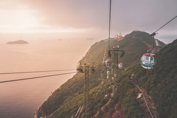 View of a cable car during beautiful sunset  in Hong Kong.  Mountain, sea or ocean landscape. Mountain covered with green forest.  Wall mural