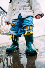 little boy walks through the puddles in the street