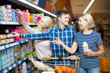 family choosing dairy products and smiling in hypermarket