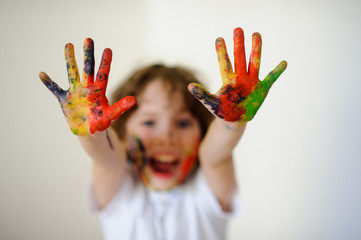 Child face and hands in the paint, he laughs