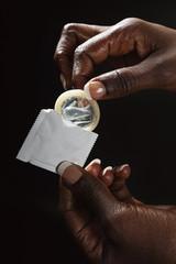 main femme noire tenant préservatif