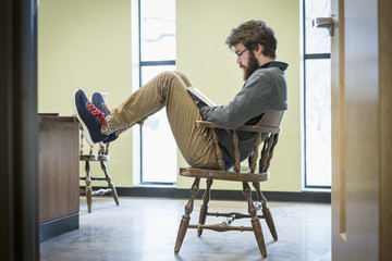 Caucasian college student reading in chair