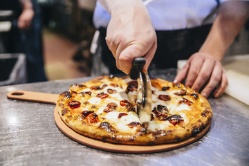 Chef making slices of pizza on pizza board in the restaurant kitchen