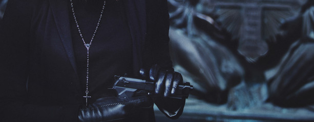 close-up hands of girls in black leather gloves, grip gun