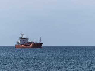 Red gas cargo ship anchoring.