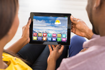 Couple Looking At Multicolored Apps On Digital Tablet