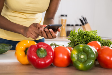 Close-up Of A Woman Using Mobile Phone In Kitchen