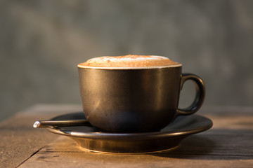 Hot cappuccino coffee cup on wooden table agent sunlight in morn