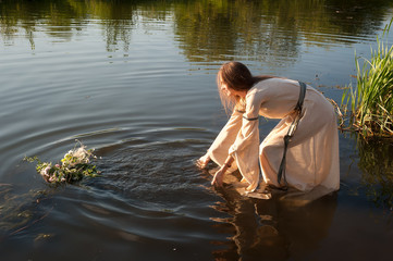 Beautiful young woman in traditional dress puts wreath in water of lake. Russian traditional Ivan Kupala holiday celebration