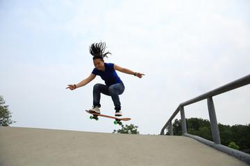 skateboarding woman practice ollie at skatepark ramp