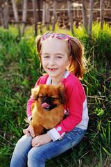 little girl smiling with hands on Pekingese
