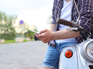 Young man sitting on scooter and using smart phone