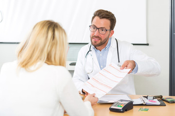 Young attractive doctor giving prescription to a patient