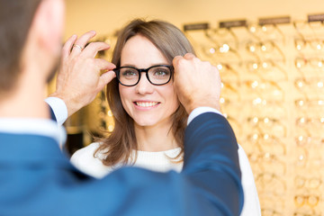 Young attractive  woman testing new glasses with optician Wall mural