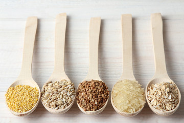 various cereals in wooden spoons on a white wooden table