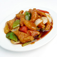 asian food - sweet and sour pork with fruit salad on white dish