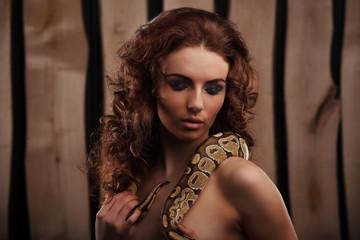 Sexy brunette girl with orange python around her neck