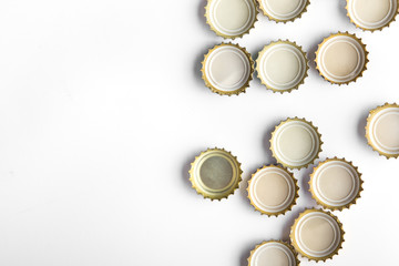 caps of beer on white background