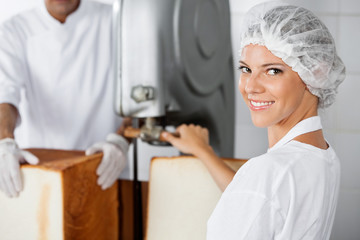 Confident Female Baker Using Cutting Machine In Bakery