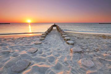 długie drewniane ryki na plaży, zachód słońca nad morzem