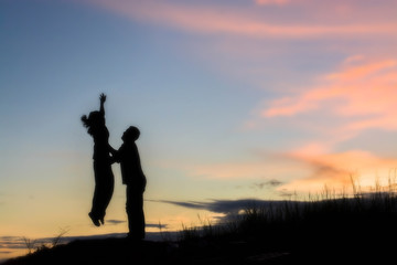Young couple silhouette jumping sunset happy time