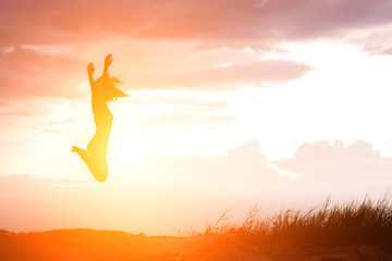 Happy woman jumping against beautiful sunset