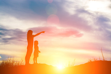 Silhouette of young mother pointed the finger to the future