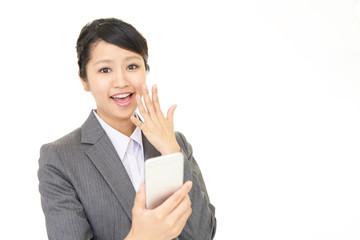 スマートフォンを持つ笑顔のビジネスウーマン