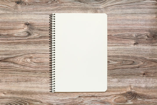 Mockup of open notepad with blank page on wooden background.